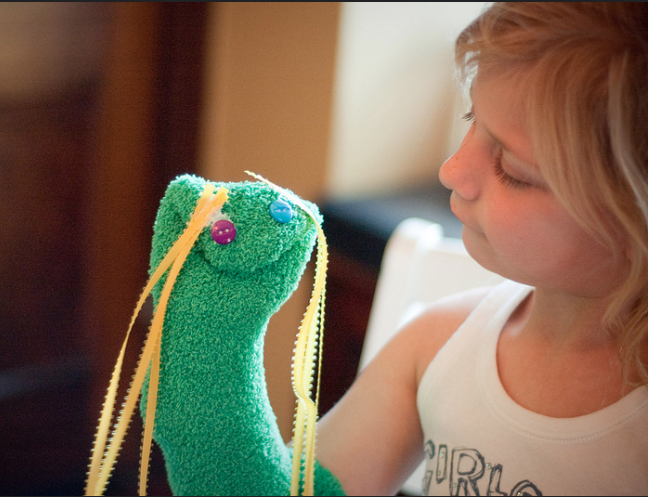 Girl with green hand sock puppet