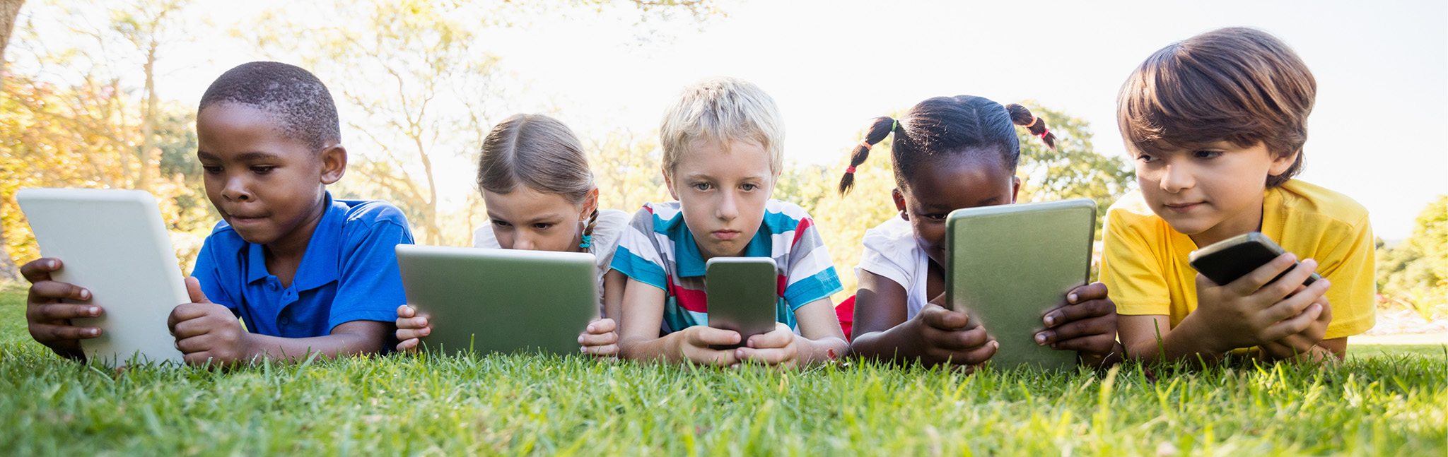5 kids with technology on grassy lawn