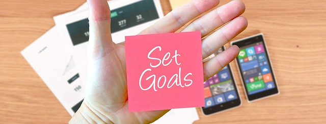 Hand with Set Goals stickie and mobile devices in the background