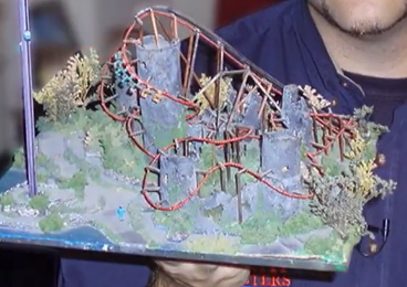 Model of a roller coaster created by and shown by a mechanical engineer named Chris Gray. He is holding a page-size board with a  handmade landscape with trees, grass, hills and the roller coaster.