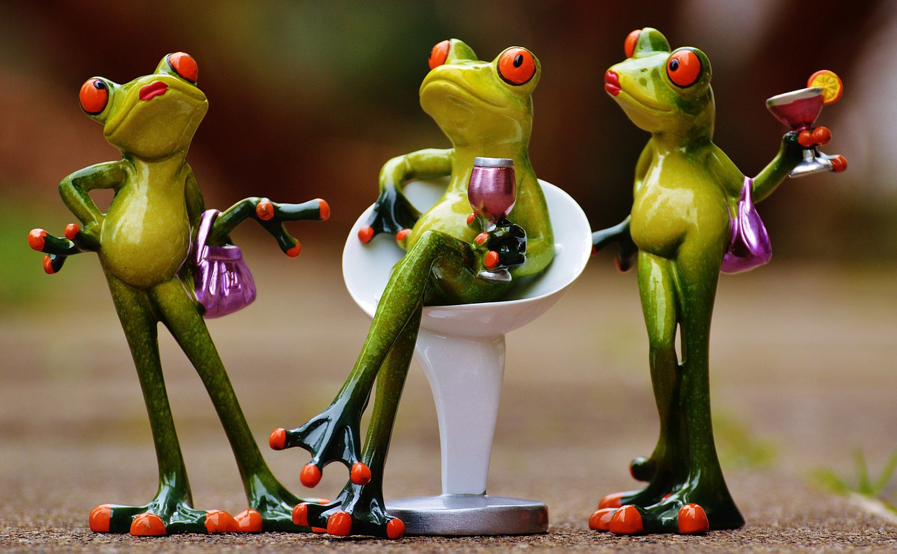 Three frogs, one sitting, in different poses.