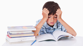 Photo of boy looking down at a book with hands to his head looking stressed.